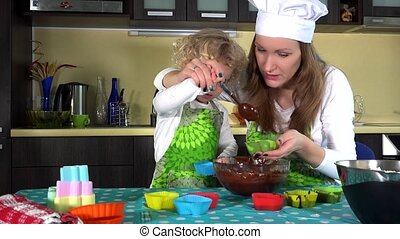 Little curly girl having fun while helping smiling mother make chocolate cake on kitchen table. Slide shot. 4K