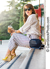 Girl having a coffee in front of her office