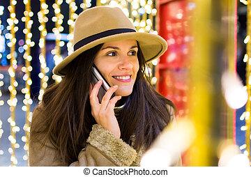 Girl having a phone call in festive environment