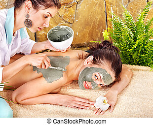 Girl having clay body mask.