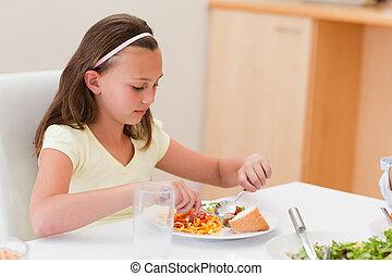 Girl having dinner at the table
