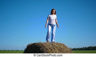 girl having fun dancing in a haystack