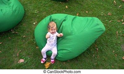 Girl having fun on beanbags in nature - Adorable toddler...