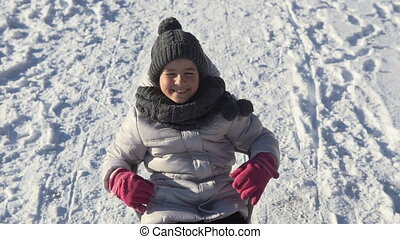 Girl Having Fun on Sledge - Smiling young girl having fun on...