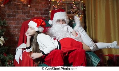 Girl having fun waving legs lying kneeling at Santa Claus sitting in a chair