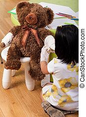 Girl having fun with teddy bear