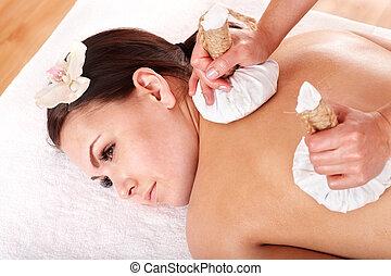 Girl having Thai herb compress massage in beauty spa. Body...