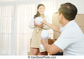 Girl helping father with packing belongings