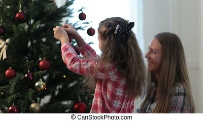 Girl helping her mom to decorate family xmas tree