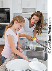 Girl helping her mother to wash utensils in kitchen - Young...