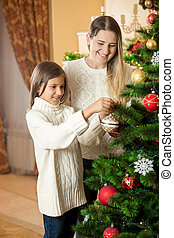 Girl helping mother to decorate Christmas tree at living room