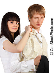 Girl helps man to dress holiday suit isolated on white background; focus on man