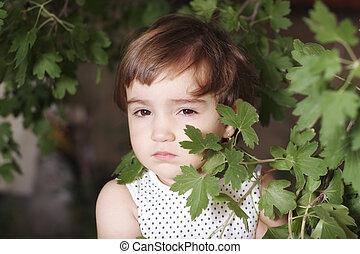 Girl hiding behind leaves
