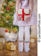 Girl hiding gift after back near Christmas tree, close-up...