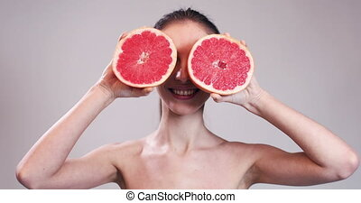 Girl Hiding Her Eyes with Grapefruit Slices - Beautiful girl...