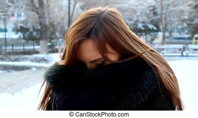 Girl hiding her face in fur coat. Young woman winter portrait. Full HD footage