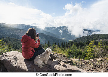 Girl hiker and dog pet in the Black Forest mountains on sunny day