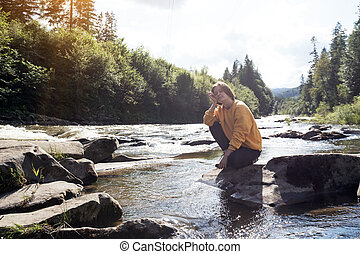 girl hiker on the bank of a mountain river