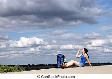 girl hiker sitting on the sand and drinking water