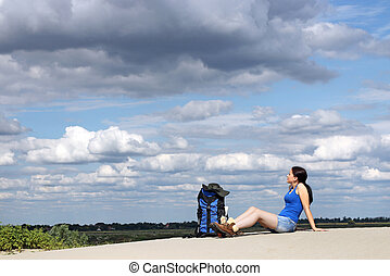 girl hiker sitting on the sand and rest
