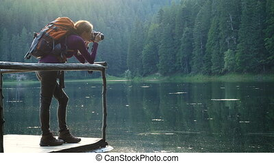girl hiker taking photo of lake