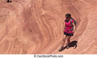 Girl hiker walking down wavy sandstone Horizontal...