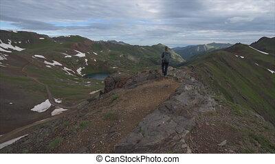 Girl Hiker walks along steep mountain ridge San Juan...