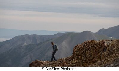 Girl Hiker walks along steep mountain ridge San Juan...