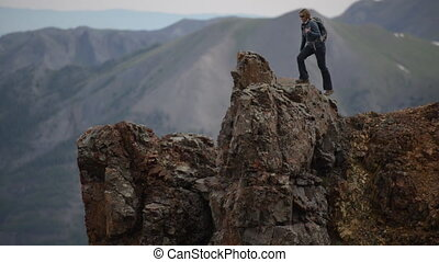 Girl Hiker walks along steep ridge to conquer the mountain