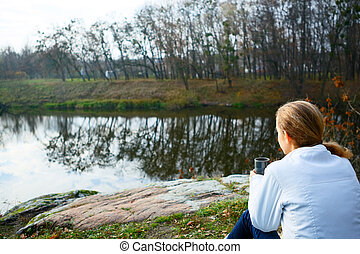Girl hiker with thermo cup of tea in hand on the autumn nature