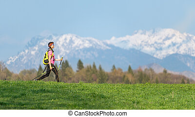 Girl hiking in the mountains with spring contrasts of green meadows and snow on the mountains