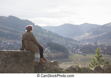 girl hipster sits on the background of mountains
