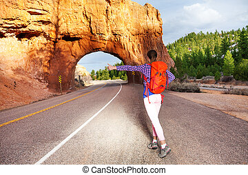 Girl hitch-hiking on the road near Red canyon