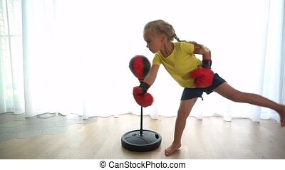 sporty girl hitting punching bag with boxing gloves on bright window background. Gimbal stabilizer movement motion shot
