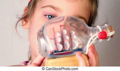 Girl hold and looks at model of tallship in glass bottle
