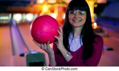 girl hold bowling ball and smile, and then throws it to beat skittles