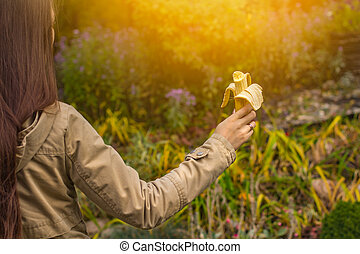 Girl holding a banana in her hand