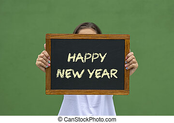 girl holding a blackboard with the message happy new year written