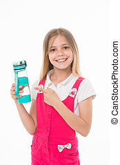 Girl holding a bottle of water. Kid with big smile wearing pink jumpsuit. Lovely child isolated on white background. Girl pointing at blue plastic bottle, healthy habits, nutrition concept