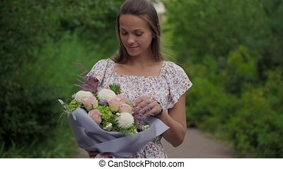 Girl holding a bouquet of fresh flowers in her hands