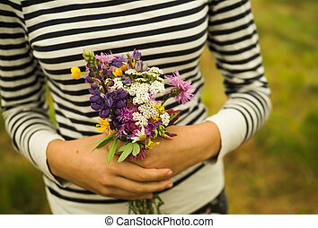 girl holding a bouquet of wild flowers.