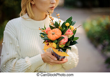 Girl holding a box of roses decorated with pumpkin
