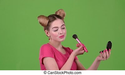 Girl holding a brush in her hand and powdering her face. Green screen. Close up