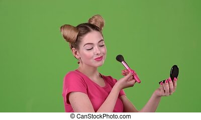 Girl holding a brush in her hand and powdering her face. Green screen. Close up. Slow motion