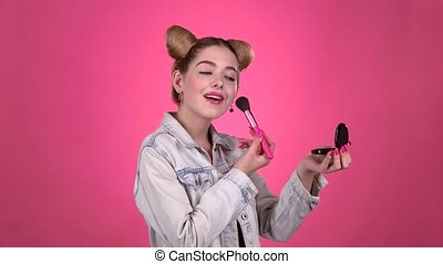 Girl holding a brush in her hand and powdering her face. Pink background