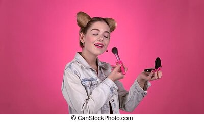 Girl holding a brush in her hand and powdering her face....
