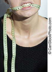 Girl holding a centimeter in her mouth