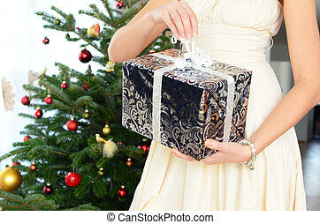 Girl holding a Christmas gift in the hands