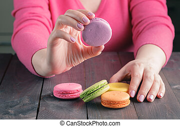 Girl holding a cup of coffee with macaroon