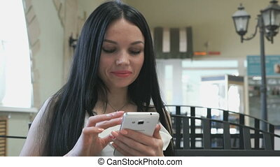 Girl holding a mobile phone in a cafe
